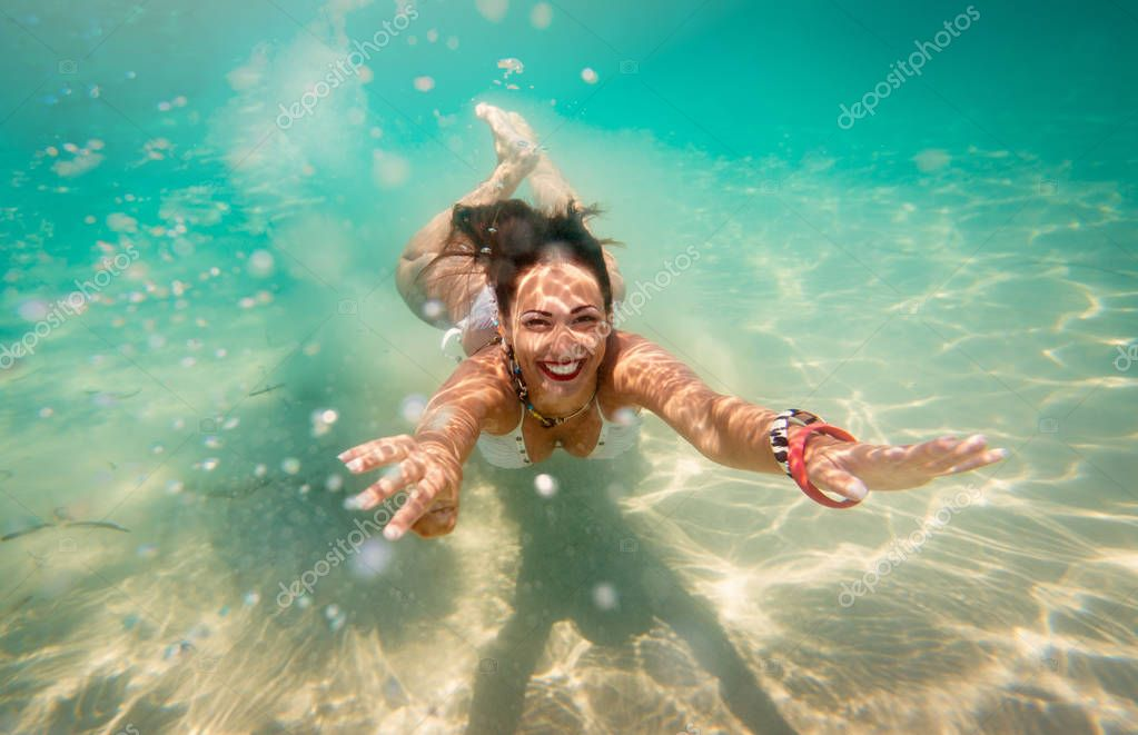 Beautiful young woman diving underwater in the sea.