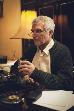 Retro senior man writer with glasses, sitting at the desk beside obsolete typewriter, with a glass of whiskey and thinking.