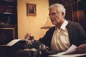 Scrittore di retrò uomo senior con i vetri e matita in mano, seduto alla scrivania e la lettura del testo per la scrittura su macchina da scrivere obsoleta.