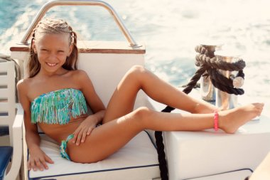 Cute smiling little girl enjoying on the deck. They are on cruise and sunbathing.