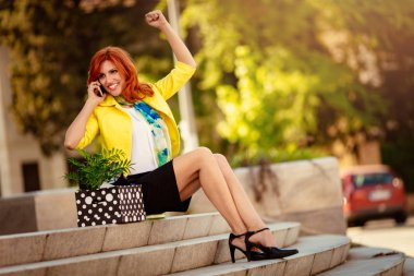 Happiness businesswoman sitting on stairs and celebrating success while talking on smartphone next to a box full of her personal belongings from the office just after she got fired.