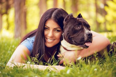 Beautiful young woman hugging her cute stafford terrier in the park and enjoying. Looking at cemera.