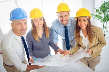 Successful young architects team discussing construction plans and planning what to change to be better. They are in the office. Looking at camera. stock vector
