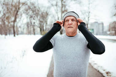 Active senior making pause and wearing hat in public park during winter training outside.