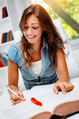 Smiling teenage girl with books learning in library