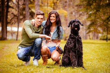 lovely couple with black schnauzer sitting in park