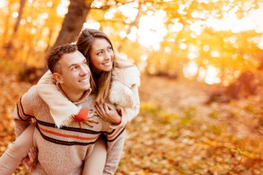 Beautiful young couple enjoying a piggyback in sunny forest in autumn colors. stock vector