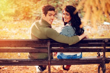 Beautiful lovely couple sitting on the bench and enjoying in sunny park in autumn colors. Looking at camera. Rear view.