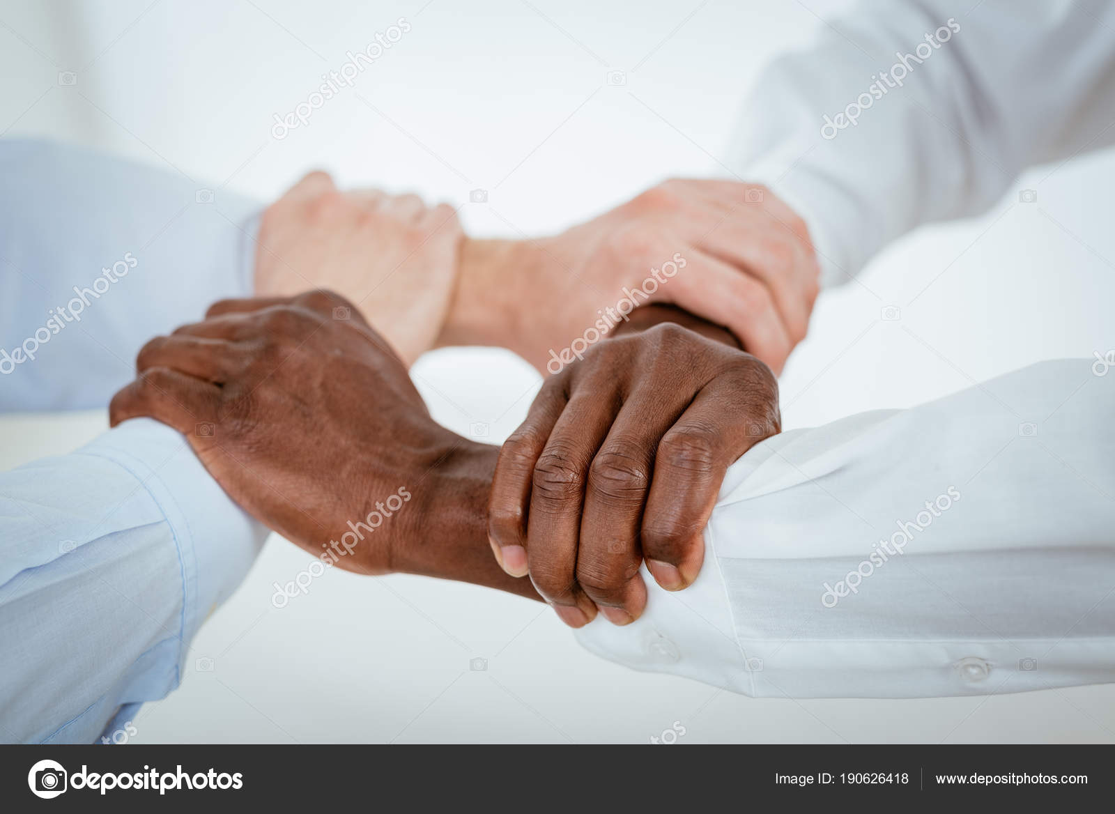 Four black white hands holding together tightly stock photo