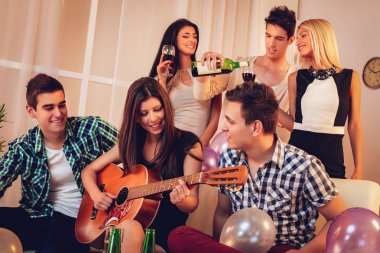 Young woman playing on guitar to friends at party