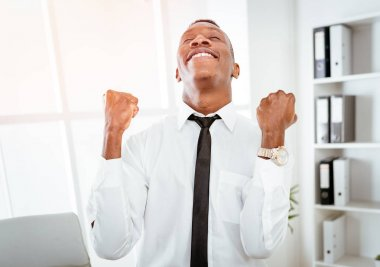 Successful African businessman celebrating success with raised arms in office