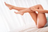 Fotografie Young woman with legs lying and relaxing on bed at home