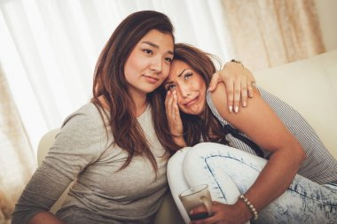 Young sad woman with problems getting support in hug best friend at apartment