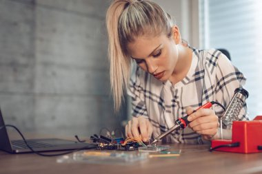 Young woman technician focused on repairing of electronic equipment by soldering iron