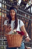 Fotografia Sorridente il messaggio della lettura della giovane donna sul smartphone sulla strada, in una giornata di sole, città guida la bici con cesto di fiori
