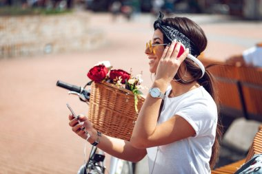 Attractive young woman is trying to find the melody she like best, during the stop of riding bike on the city street. She is glad of doing this.