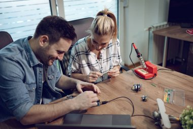 Man helping woman soldering elements of circuit board