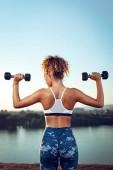 Fotografie Pohled zezadu na mladých fitness žena dělá cvičení s činkami