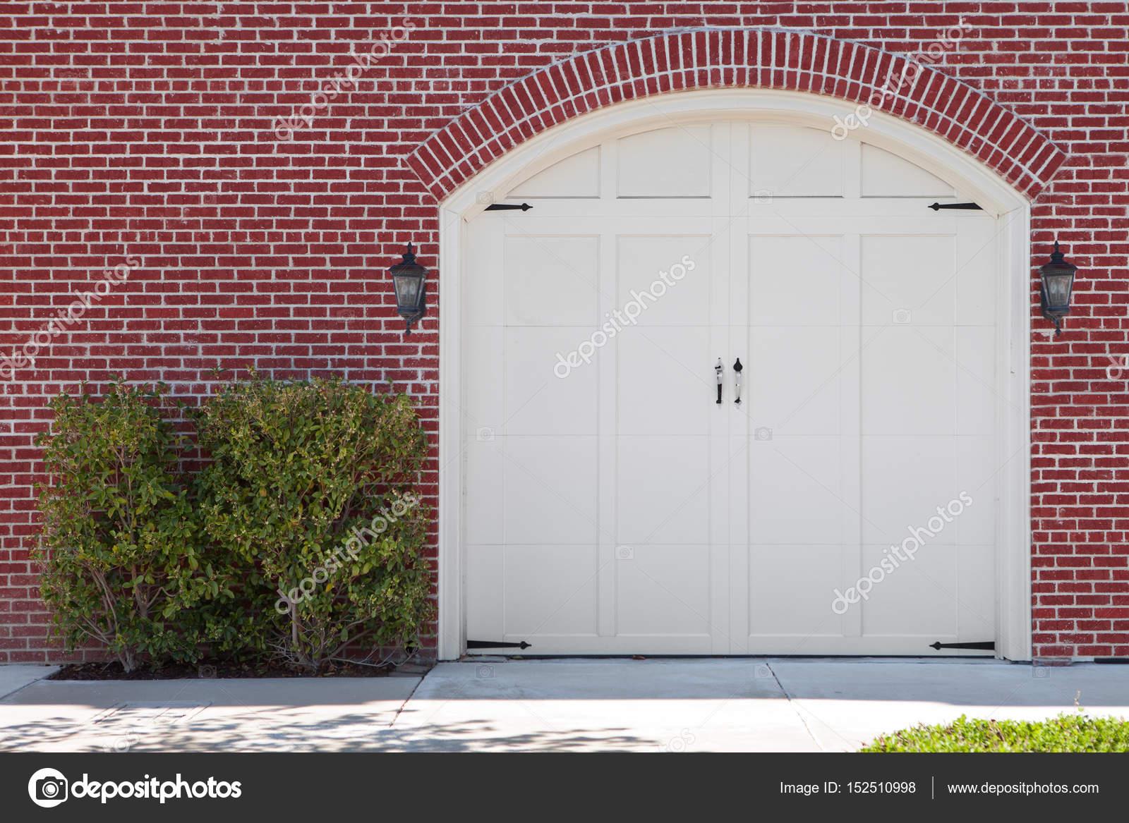 Houten Garagedeuren Prijs : Weergave van witte houten garagedeuren en rode bakstenen muren
