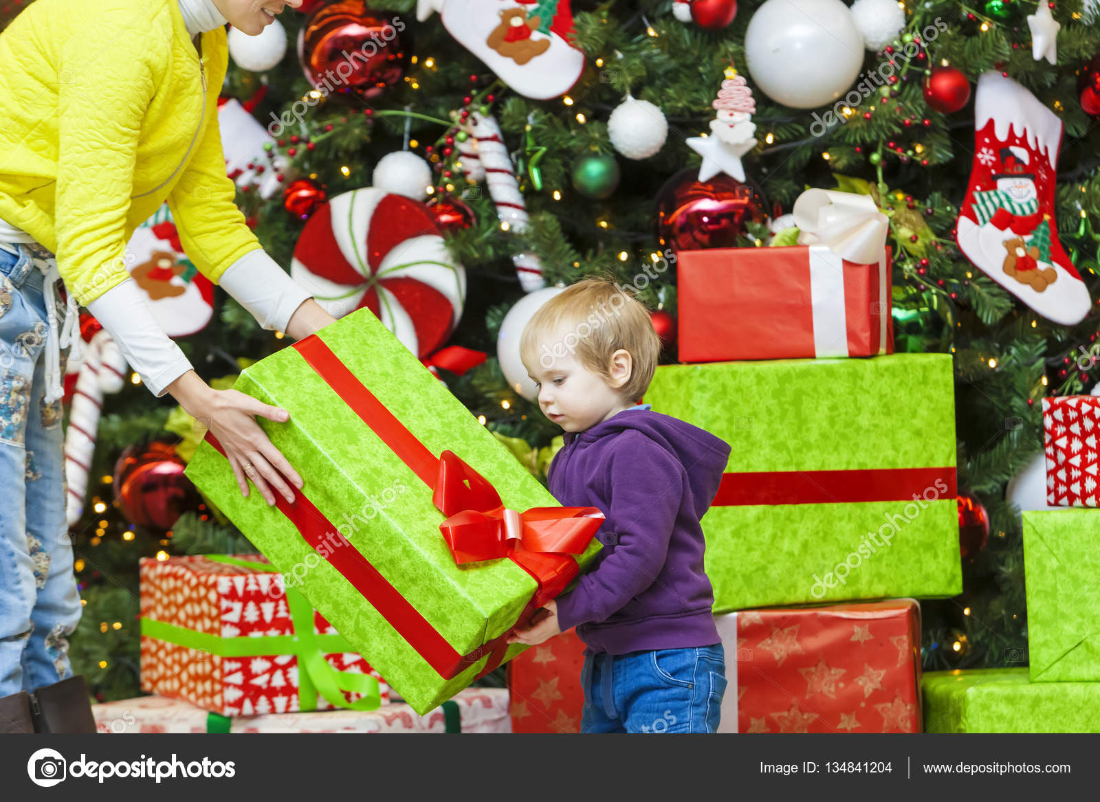 mom gives a gift to kid on the background of the christmas t stock photo