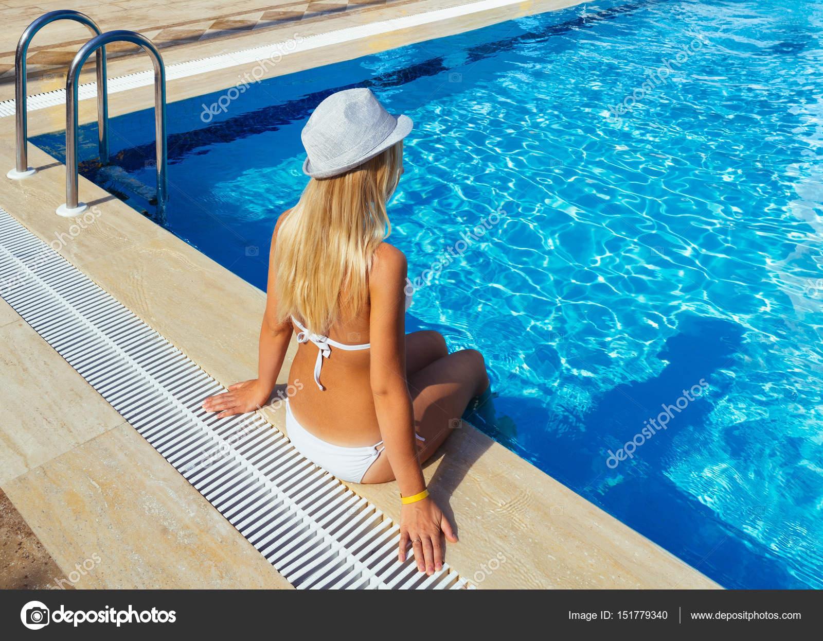 Chica rubia sentada junto a la piscina fotos de stock for Fotos follando en la piscina