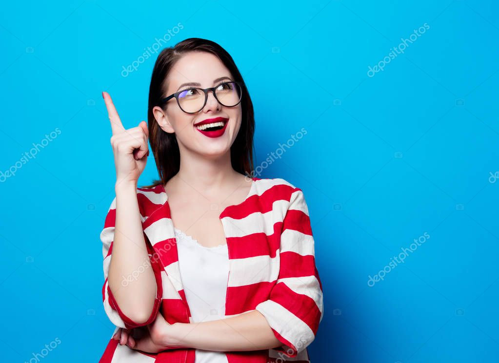 Portrait of the beautiful young smiling woman on the blue backgr