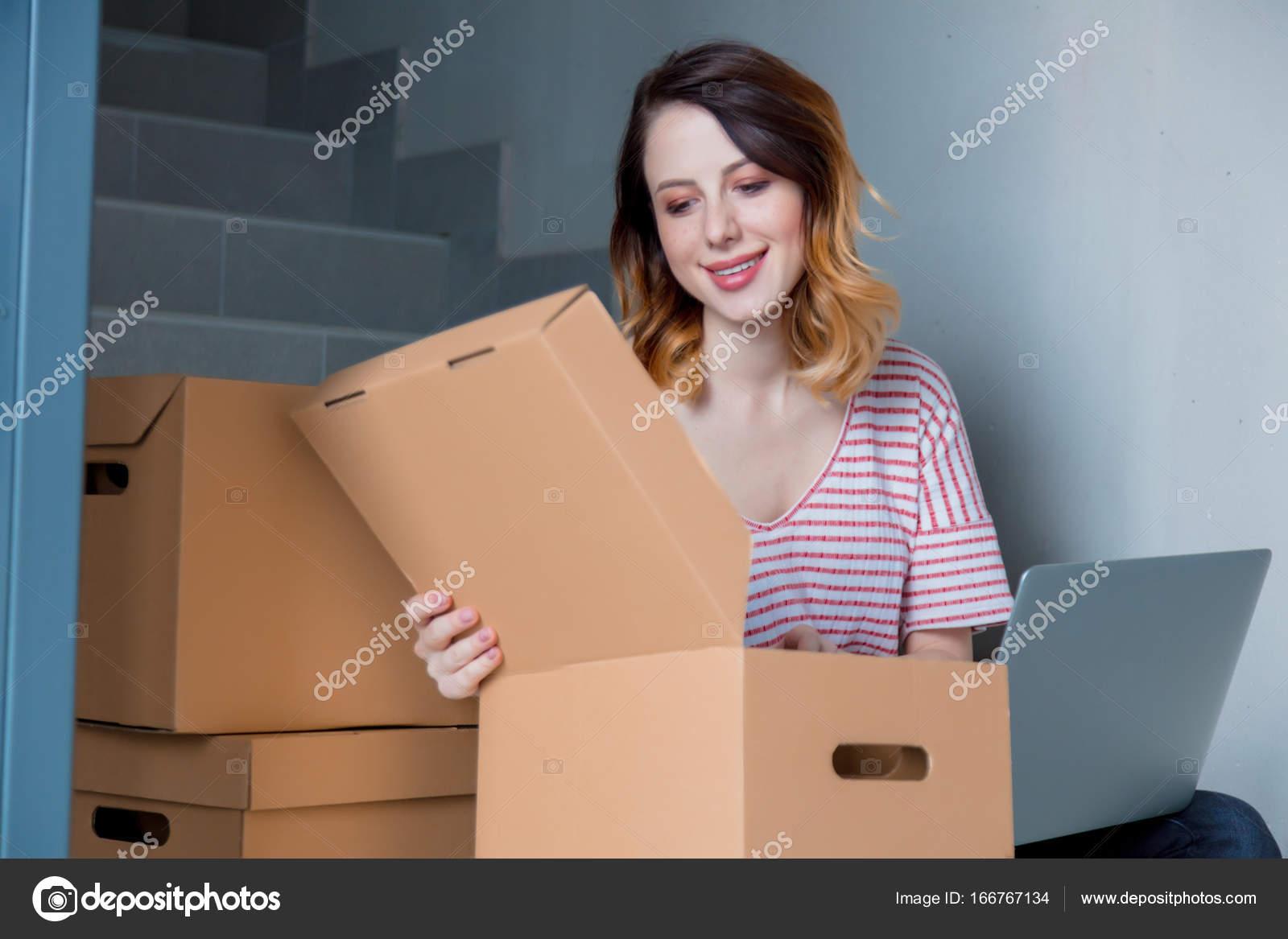 femme en ouvrant la bo te en carton de d m nagement photographie massonforstock 166767134. Black Bedroom Furniture Sets. Home Design Ideas