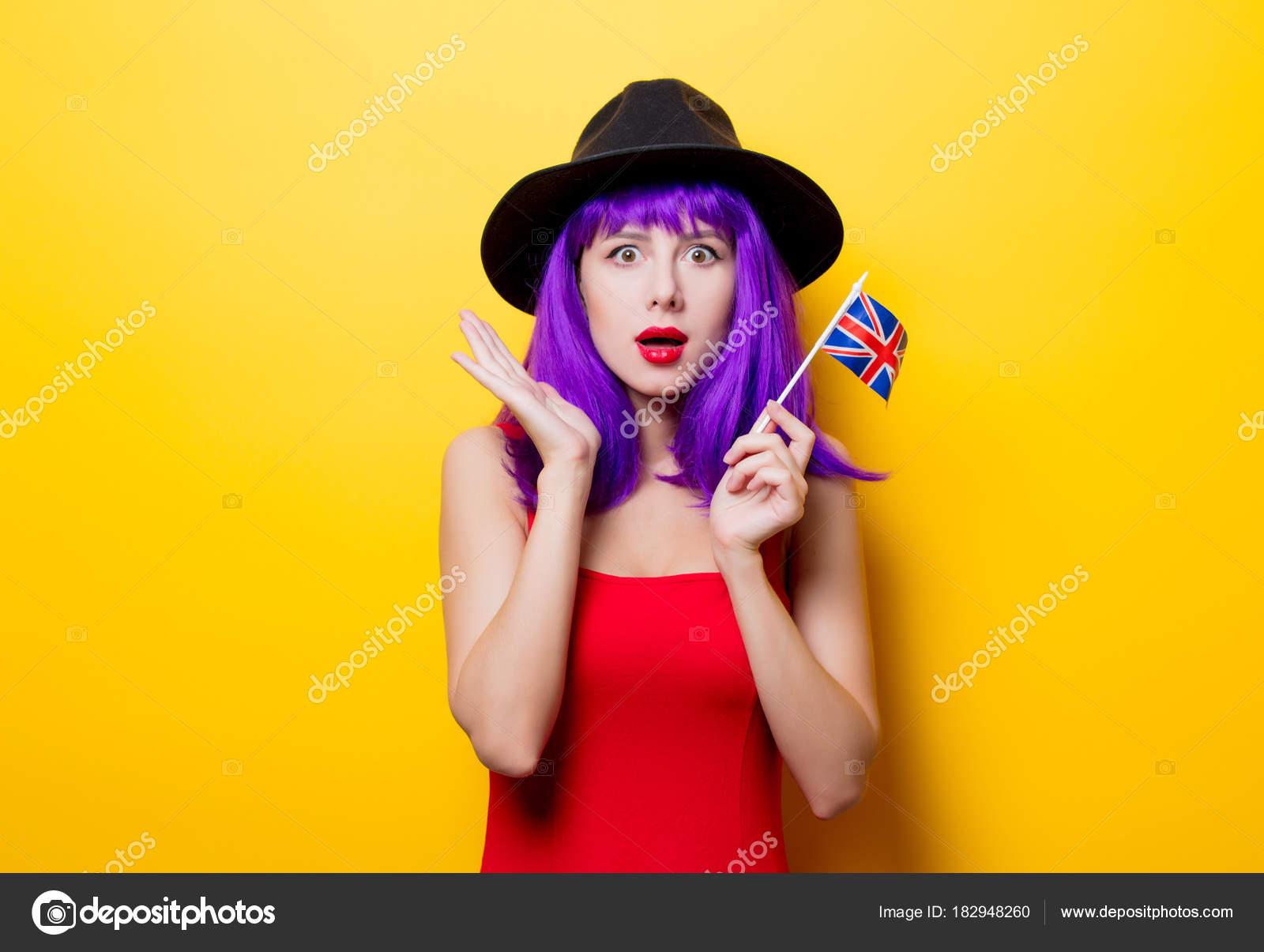 Ritratto di giovane stile hipster ragazza con taglio di capelli viola e  bandierina della Gran Bretagna in mano su priorità bassa gialla– immagine  stock 0916e35d005d