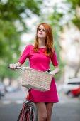 Fotografie Portrét dívky zrzka v sluneční brýle s kolo ve městě