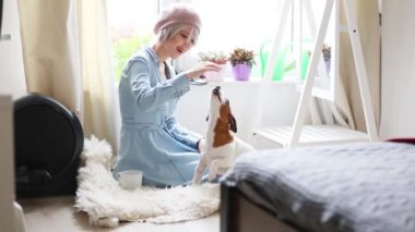 Young girl with pink hair and beret with dog at home. Trendy style clothes