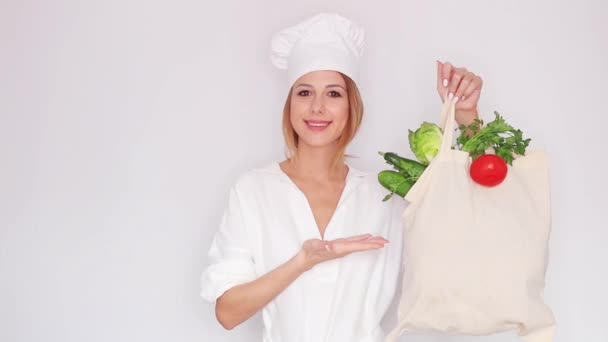 woman in cook uniform holding with different vegetables