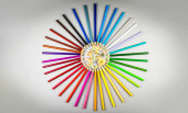Mnohobarevné tužky jsou uspořádány v kruhovém tvaru s dřevěným