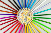 Multicolored pencils are arranged in a circle shape with wooden