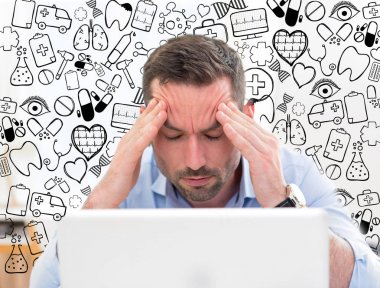 Businessman got headache because of burn out surrounded by icons