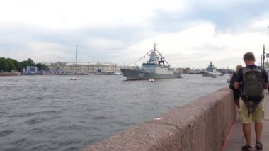 Tourist taking pictures on a smartphone warships on the Neva river. The eve of Navy Day in St. Petersburg