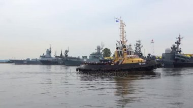 The tug with military sailors on the background of the ships of the Baltic fleet. Preparation for Navy Day in Kronstadt