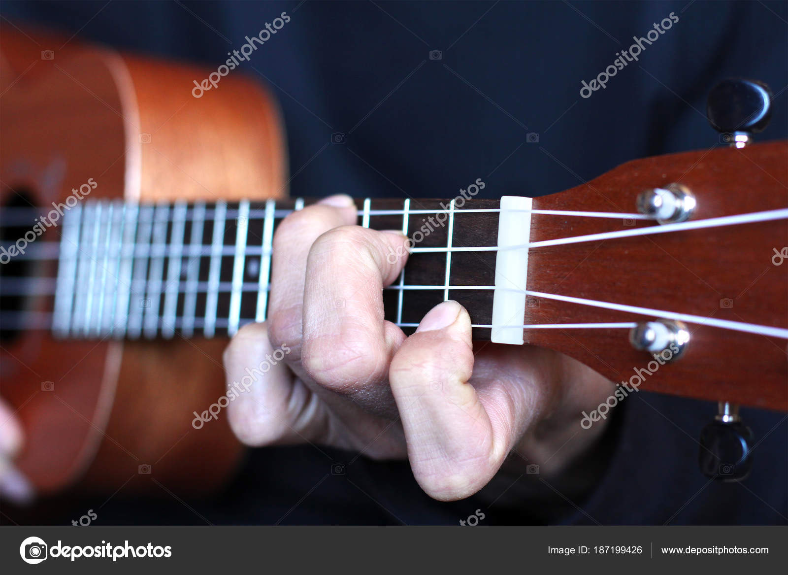 Left Musician Hand Clamps The Chord On The Ukulele Fretboard Stock