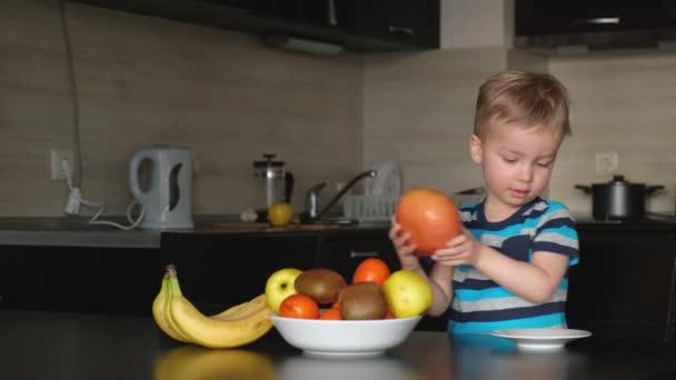 malé dítě vybrat čerstvé ovoce pro ranní vegetariánské snídaně, místo grapefruit na talíři a šťastný, vegan dítě u stolu v kuchyni, chlapec se zdravým jídlem bohaté na vitamín pro imunitu