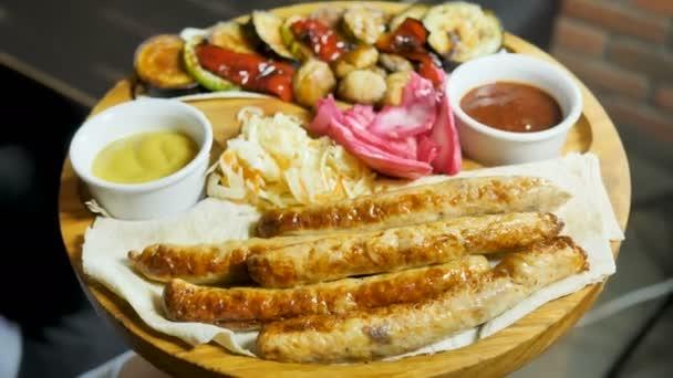 Grilování klobásy s přidáním bylinek a zeleniny na gril talíř, venku. Grilování potravin, velký q, gril, 4k