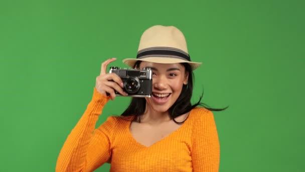 Hezká asijská žena ve stylovém oblečení aktivně fotí přes retro kameru na zeleném pozadí. Koníčky, volný čas, oblíbená zábava. Zábava, relaxace, fotoset. Ženský portrét