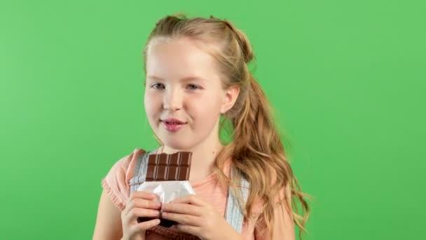Detailní pohled na legrační dívku, jak jí čokoládovou tyčinku. Hnědé rty a zuby. Dítě si olizuje rty