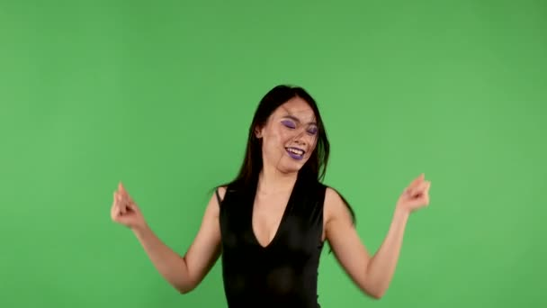Energetic happy young asian woman smiling and dancing against green background throwing up her long black hair with her hands