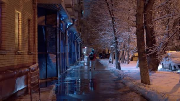 City street on a winter snowy night. The sidewalk is covered with water and ice, drops are falling from the roof. The light of lanterns is reflected in asphalt. Unrecognizable people