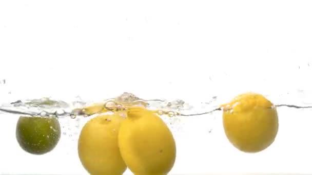 Zavřete čerstvé citrony padající do vody s velkým šplouchnutím a bubliny na bílém pozadí. Zpomalený pohyb