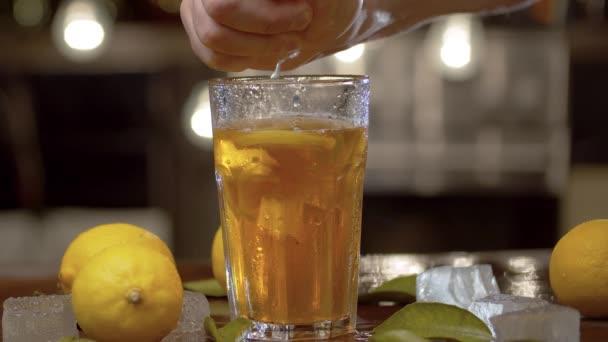 Zblízka mužská ruka mačkat citron do sklenice s ledovým čajem nebo koktejlem. Sklenice s osvěžujícím nápojem, ledem, citróny a listí na stole na rozmazaném pozadí