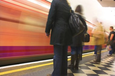 busy underground station platform train coming by fast