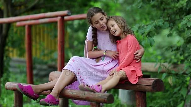 Dvě sestry sedí na dřevěný