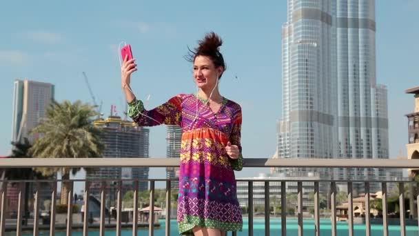 Woman stands near megatall skyscraper