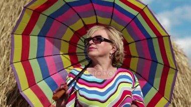 Blond žena v sluneční brýle s deštníkem