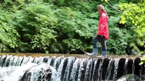 Mädchen läuft am kleinen Überlaufdamm entlang